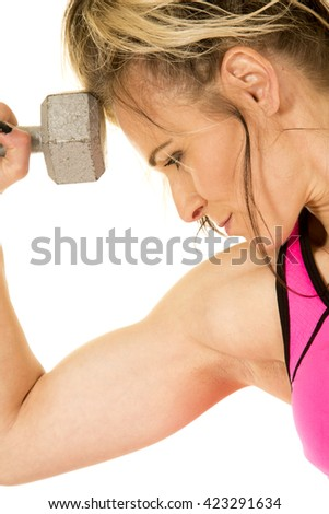 A close up of a woman with a dumbbell next to her head, flexing her bicep. - stock photo