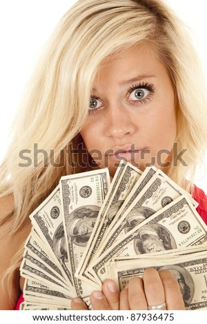 A close up of a woman with a serious expression on her face holding up a fan full of one hundred dollar bills.