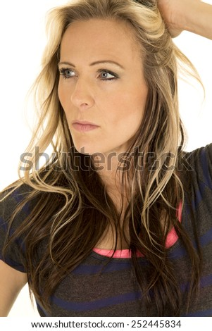A close up of a woman with a serious expression on her face, playing with her hair. - stock photo