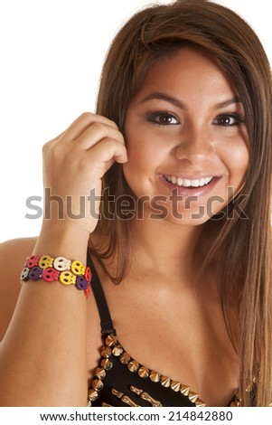 A close up of a woman with a smile on her face, wearing a many colorful skull bracelet around her wrist. - stock photo