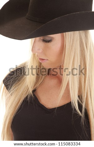 A close up of a woman with her cowgril hat on looking down. - stock photo