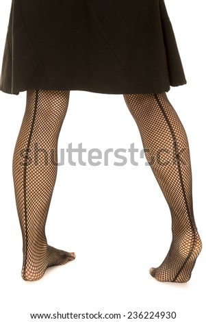 A close up of a womans legs in black fishnet stockings from the back. - stock photo