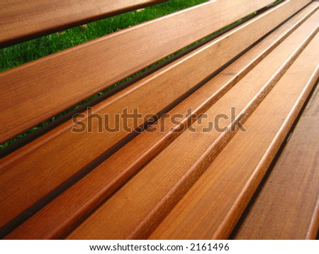 A close up of a wooden bench in the park.