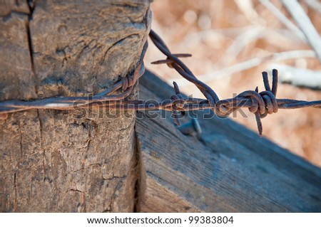 A Close Up of a Wooden Fence with Barbed Wire - stock photo
