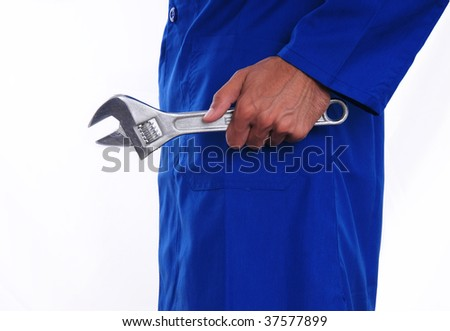 A close up of a worker holding a wrench by his side. The man is wearing a blue jumpsuit. - stock photo