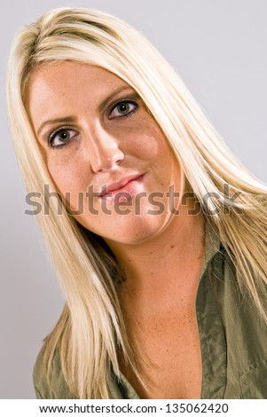 A close up of a young Caucasian blonde female facing left of camera with her head turned to the camera and smiling. - stock photo