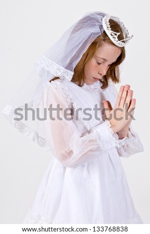 A close-up of a young girl praying in her First Communion Dress and Veil - stock photo