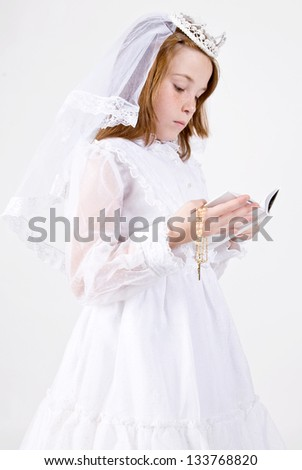 A close-up of a young girl smiling in her First Communion Dress and Veil, reading a bible while holding her rosary beads with a cross - stock photo