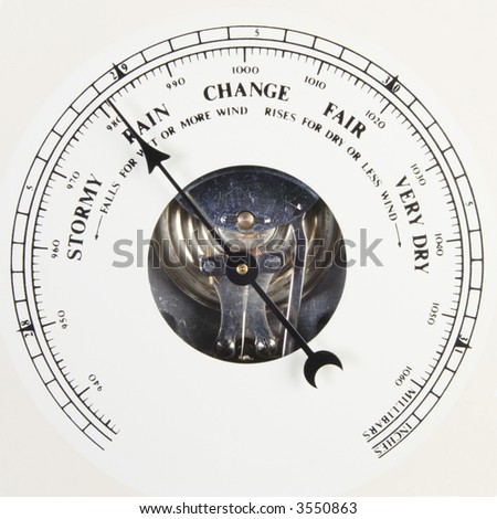 A close up of an aneroid barometer with the dial set to rain - stock photo