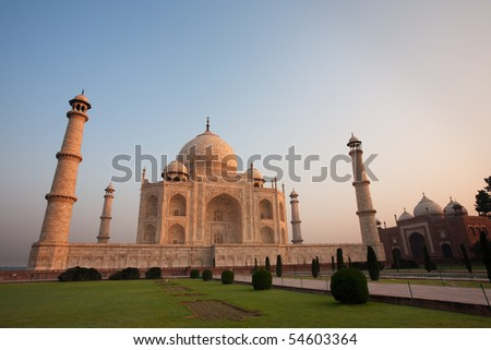 A close-up of an empty front Taj Mahal, wide lawn and the jawab building reflecting morning glowing orange sunrise light with a clear blue dawn sky at Agra, India. Horizontal copy space - stock photo