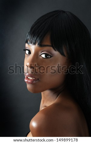 A close-up of an extraordinarily beautiful young black woman with amazingly captivating eyes. - stock photo
