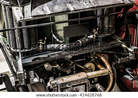 A close up of an old retro engine / classic car engine, retro vehicle motor and work metal parts, vintage industrial steampunk close-up old cars
