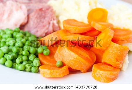 A close-up of boiled sliced carrots with peas on a white plate - stock photo