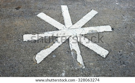 A close up of cracked white asterisk on asphalt road.  Picture can be used as a background. - stock photo