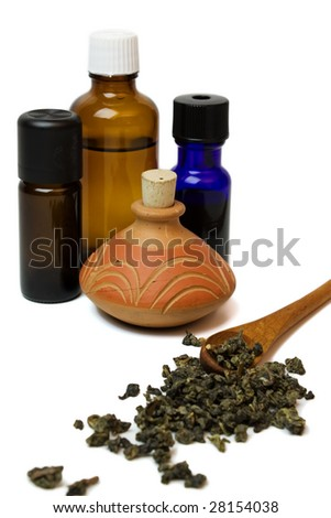 A close up of essential oil bottles and dried herbs on a white background. - stock photo