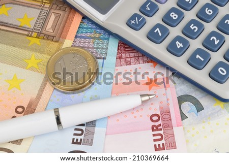 A close up of Euro notes and coins, with a calculator and pen.