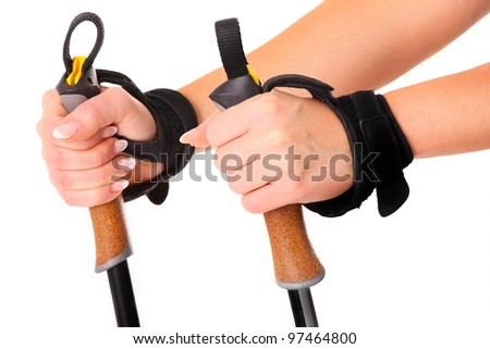 A close-up of female hands holding nordic walking sticks over white background - stock photo