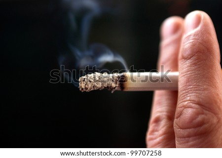 a close-up of fingers holding a cigarette - stock photo
