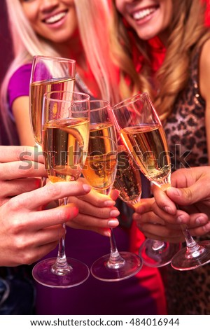 A close up of five hands clinking glasses with champagne, two girls are in the backgrounds