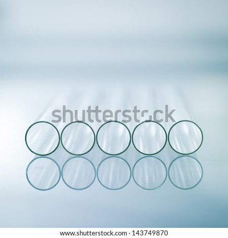 A close-up of five horizontal medical test tubes on a light blue gradient background - stock photo
