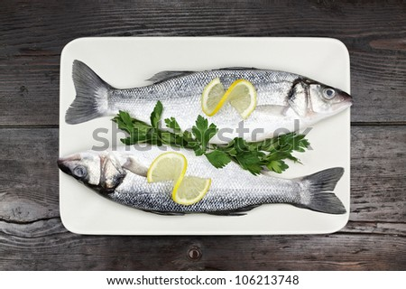A close up of fresh sea bass on a wooden surface. - stock photo