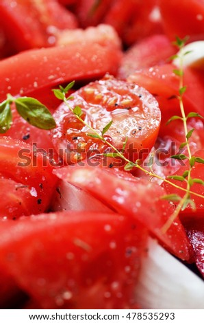 A close-up of fresh sliced tomatoes, garlic, onion, herbs and olive oil