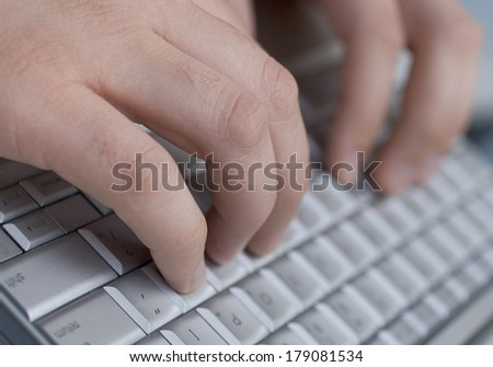 A close up of hands typing on a keyboard. - stock photo