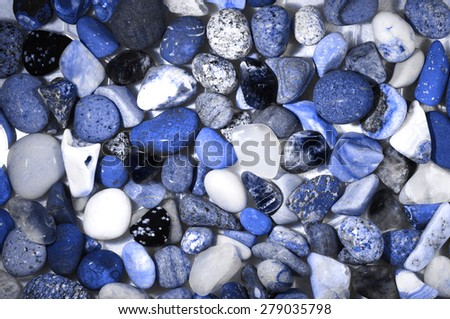A close up of pebbles and stones on a sea shore or rock pool in colorful shades of blue and white - stock photo