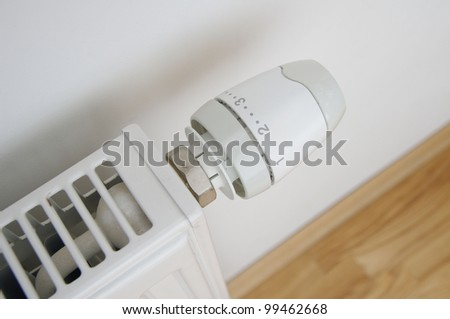 a close up of radiator regulator knob set to second level with wooden floor and wall visible - stock photo