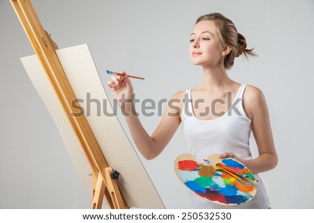 A close-up of smiling girl who  paints on canvas with oil colors. Isolated. - stock photo
