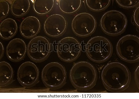 a close up of stacked wine bottles' bottoms - stock photo