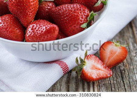 A close up of strawberries in a bowl with a sliced strawberry on the side.