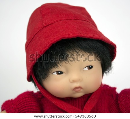 A close up of the face of a Chinese baby doll dressed in red.