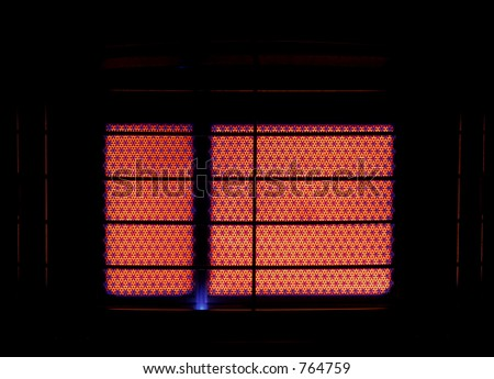 A close up of the heating ceramic of a switched on gas heater, with a silhouette of the grilel.