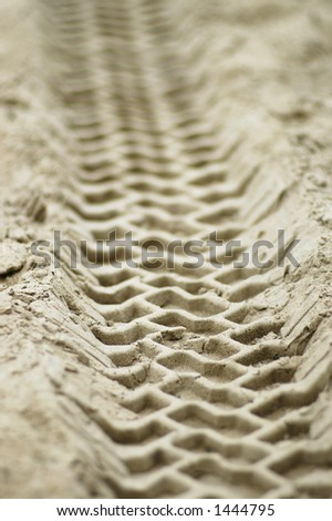 A close-up of the impression left by a vehicle driving over sand. - stock photo