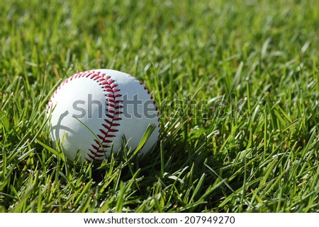 A close up of the red stitching on a baseball, laying in green grass