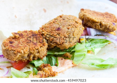 A close-up of three falafels sat on a salad on an open wrap
