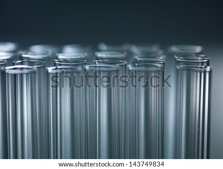 A close-up of three rows of vertical tubes on a dark grey gradient background - stock photo