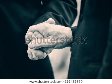 A close up of two married men holding hands at their wedding.  Lightly Toned.  - stock photo