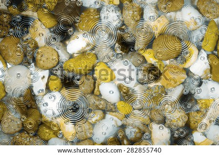 A close up of water covered pebbles and stones in shades of brown and white in a river bed or pond with rain ripples