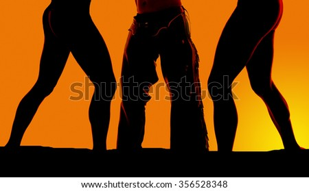 A close up of women's legs with a cowboy in his chaps. - stock photo