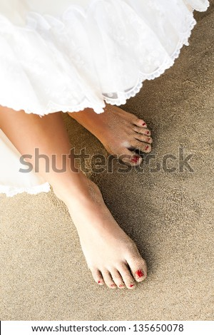 a close-up on a dress being lift up to reveal slim sandy feet with red toenails - stock photo