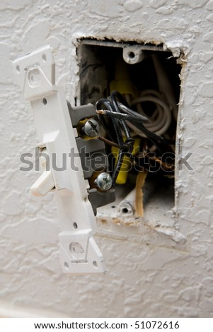 A close up on a light switch with damaged wiring - stock photo