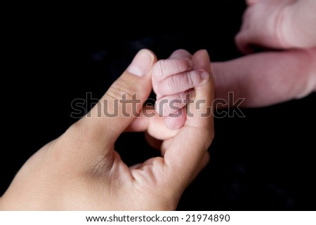 A close up on hands and fingers of a newborn baby and its mother.