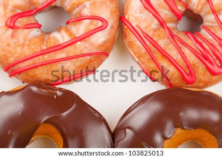 A close-up overhead view of four chocolate and cherry donuts.