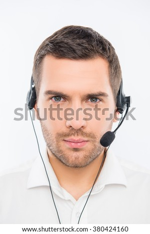 A close-up photo of serious young agent of call centre - stock photo
