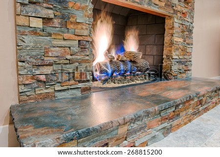 A Close up photo of the fire in a fireplace showing the details of the texture wall and tiles