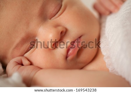 A close-up photograph of a sleeping newborn baby's face. It's a selective focus image, with the focus being on the infant's tiny lips.