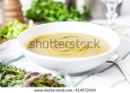 A close up photograph of a white bowl with classic vegetarian potato and leek soup decorated with olive oil. Green parsley, wood peppermill and sliced leek on background. White rustic wood background - stock photo