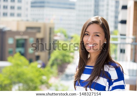 A close-up picture of a beautiful happy woman relaxing on a summer day on a balcony of a new apartment, on a city background - stock photo